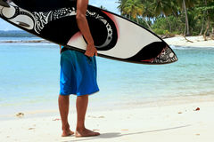 Surfer on beach with funky arty surfboard Royalty Free Stock Images