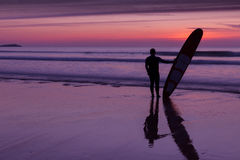 Surfer on beach holding surfboard at sunset. Silhouette of a surfer on coast in the evening light royalty free stock photography