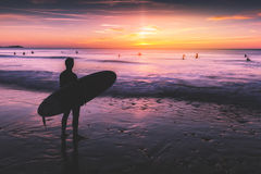 Surfer on beach holding surfboard at sunset. Silhouette of a surfer on coast in the evening light royalty free stock image