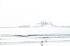 Surfer on the beach with industrial background Royalty Free Stock Photo
