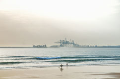 Surfer on the beach with industrial background Royalty Free Stock Photos