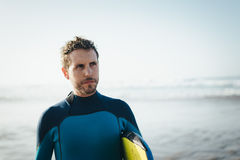 Surfer beach portrait. Male surfer beach lifestyle portrait. Man in wetsuit with bodyboard surfing equipment Stock Photo