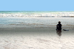 Surfer on beach. Surfer sitting on the ocean beach at sunset in conil, spain Royalty Free Stock Photography