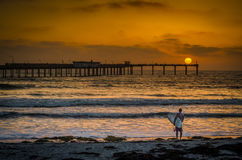 Surfer on the beach at sunset in San Diego California. Surfer looking out at ocean in San Diego sunset with pier in background Royalty Free Stock Photos