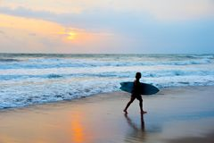 Surfer at beach with surfboard Royalty Free Stock Images