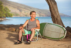 Surfer on Beach with Surfboard. Handsome male surfer sitting on beach near his surfboard Stock Image