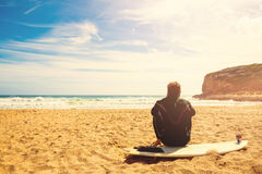 Surfer on the beach waiting for perfect waves. Surfer on the beach sitting on surfboard and waiting for perfect waves Royalty Free Stock Image