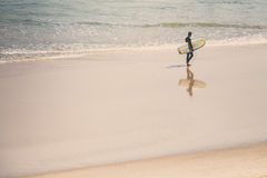 Surfer on beach. A surfer walking the beach Royalty Free Stock Photography