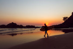 Surfer on beach. A surfer walking towards the water at a beach sunrise Royalty Free Stock Photography