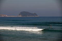 Surfer beach of Zarautz with people surfing in front of Getaria. Surfer beach of Zarautz with people surfing in front of the town and port of Getaria, Guipuzcoa Stock Images