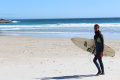 Surfer. A bearded hip surfer in wetsuit walks up the beach with this surfboard on Llandudno Beach, Cape Town, South Africa stock photo