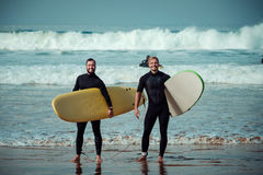 Surfer beginner and instructor on a beach with a surfboards.  Stock Photography
