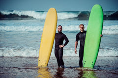 Surfer beginner and instructor on a beach with a surfboards Royalty Free Stock Photos