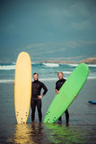 Surfer beginner and instructor on a beach with a surfing boards.  Stock Photos