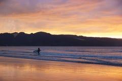 Surfer bei Sonnenuntergang auf dem 90 Meilen-Strand, Ahipara, Neuseeland Stockfotos