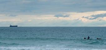 Surfer betrachten das Schiff weit weg Lizenzfreie Stockfotos