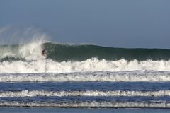 Surfer on a big wave at Porthtowan. A surfer riding a big wave at Porthtowan beach on the north Cornwall coast, a popular holiday UK destination for water sport Royalty Free Stock Photo