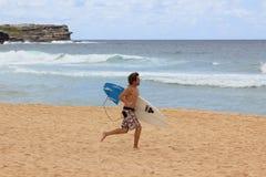 Surfer bij strand het lopen Stock Foto