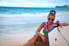 Surfer bikini woman on beach. Beach lifestyle people - woman enjoying summer, sitting on the Waimanalo beach relaxing with surfboard after bodyboarding in water Royalty Free Stock Images
