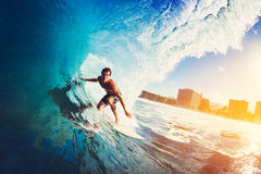 Surfer on Blue Ocean Wave. Getting Barreled at Sunrise Royalty Free Stock Image