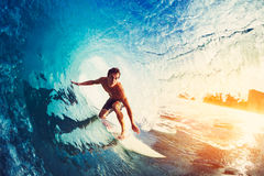 Surfer on Blue Ocean Wave. Getting Barreled at Sunrise Stock Photography