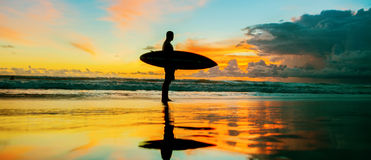 Surfer with board. Young surfer with board on the beach royalty free stock photo
