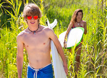 Surfer boy and girl walking in the green jungle Royalty Free Stock Photo