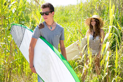 Surfer boy and girl walking in the green jungle Royalty Free Stock Photography