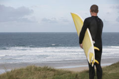 Surfer Carrying Surfboard On Beach Looking At Sea. Rear view of male surfer carrying surfboard on beach looking at sea Royalty Free Stock Images