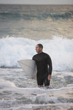 Surfer Carrying Surfboard Out From Sea Stock Image