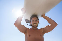Surfer carrying surfboard over head against blue sky. Portrait of surfer carrying surfboard over head at beach coast against blue sky Stock Photo