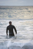 Surfer Carrying Surfboard Into Sea Royalty Free Stock Image
