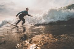 Young man surfing a wave at sunset. Surfer catching an ocean wave during sunrise. Extreme water sports and outdoor active lifestyle. Vintage filter with soft Royalty Free Stock Photo