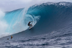 Surfer catching wave during championships in Teahupoo, Tahiti Royalty Free Stock Images