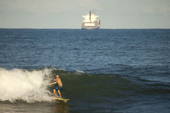Surfer catching a wave, Durban. A surfer catching a wave in Durban. A Cargo ship in the background Stock Image