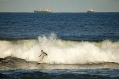 A surfer catching a wave, Durban. Cargo ships can be seen in the distance Royalty Free Stock Photography