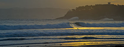 Surfer catching waves at dawn in Santander Stock Photo