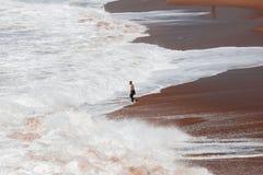 Surfer on the coast between crashing waves in Cadiz, Spain royalty free stock image