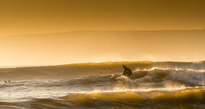 Surfer at Compton Bay, Isle of Wight. Surfer catching the last waves before Sundown Stock Image