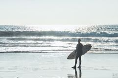 Surfer contemplates a wave at shore Royalty Free Stock Photos