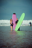 Surfer couple on the beach with a surfing board.  Royalty Free Stock Photography