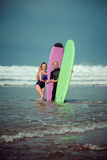 Surfer couple on the beach with a surfing board.  Stock Image