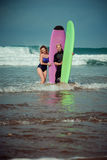 Surfer couple on the beach with a surfing board.  Royalty Free Stock Image
