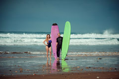 Surfer couple on the beach with a surfing board.  Royalty Free Stock Photos