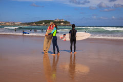 Surfer couple carrying their surfboard on the beach. SANTANDER, SPAIN - AUGUST, 20: Surfer couple carrying their surfboard on the beach on August 20, 2016 Stock Photography