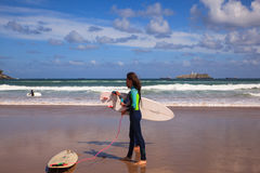 Surfer couple carrying their surfboard on the beach. SANTANDER, SPAIN - AUGUST, 20: Surfer couple carrying their surfboard on the beach on August 20, 2016 Stock Images