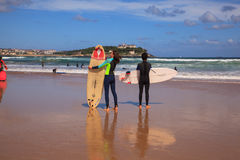 Surfer couple carrying their surfboard on the beach. SANTANDER, SPAIN - AUGUST, 20: Surfer couple carrying their surfboard on the beach on August 20, 2016 Stock Photo