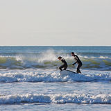 Surfer Couple. SAUNTON SANDS, ENGLAND - DECEMBER 3, 2014: Surfing couple riding the waves in unison. The bay in North Devon is popular with surfers and boarders Stock Photography