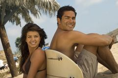 Surfer couple sitting back to back. Against surfboard on beach Stock Photography