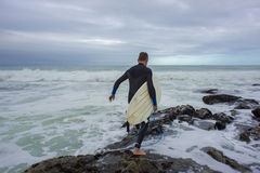 Surfer Crossing the Rocks Royalty Free Stock Image